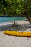 Muchacha en el oscilación en una playa Foto de archivo