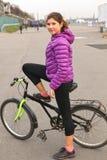Muchacha en el parque de la ciudad con la bicicleta Imagen de archivo