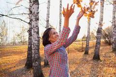 Muchacha en el parque del otoño que juega con las hojas Imagenes de archivo