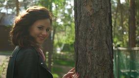 Muchacha en el parque, en el fondo de árboles La muchacha adolescente mira abajo, después cepilla el pelo detrás de su oído, y lo metrajes