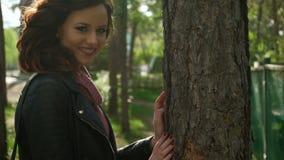 Muchacha en el parque, en el fondo de árboles La muchacha adolescente mira abajo, después cepilla el pelo detrás de su oído, y lo almacen de metraje de vídeo
