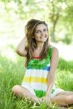 Muchacha en el parque en la hierba verde. Imagen de archivo libre de regalías