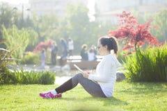 Muchacha en el parque usando la tableta Foto de archivo libre de regalías