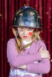 Muchacha en el payaso Make Up y casco con los brazos cruzados Fotos de archivo libres de regalías