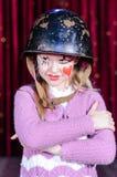 Muchacha en el payaso Make Up y casco con los brazos cruzados Imagen de archivo libre de regalías