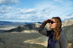Muchacha en el pie de las montañas que miran en la distancia Foto de archivo libre de regalías