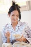 Muchacha en el pijama que come cereal Foto de archivo