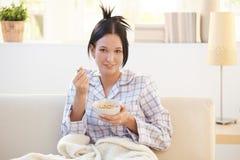 Muchacha en el pijama que desayuna el cereal en el sofá Foto de archivo libre de regalías