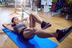 Muchacha en el piso que hace ejercicios en el estómago en el gimnasio B mojado Fotos de archivo