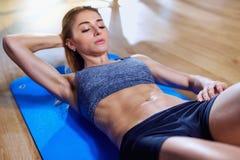 Muchacha en el piso que hace ejercicios en el estómago en el gimnasio B mojado Imagenes de archivo