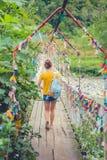 Muchacha en el puente Puente colgante de la cuerda Cuerda coloreada Fotografía de archivo