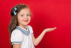 Muchacha en el rojo que muestra algo en la palma Fotografía de archivo libre de regalías