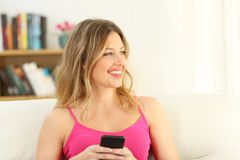 Muchacha en el rosa que sostiene un teléfono elegante que mira el lado Fotos de archivo