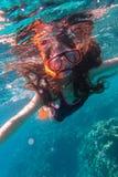 Muchacha en el salto de la máscara de la natación en el mar cerca del arrecife de coral imagen de archivo libre de regalías
