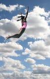 Muchacha en el salto del traje de baño en cielo Imagen de archivo