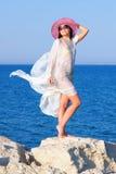 Muchacha en el sarong blanco que se coloca en la piedra grande Foto de archivo