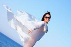 Muchacha en el sarong blanco que se coloca en la playa Imagenes de archivo