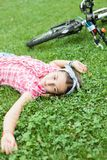 Muchacha en el sittind del parque abajo en la hierba Fotografía de archivo libre de regalías