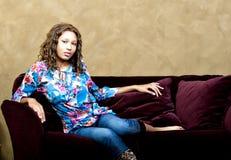 Muchacha en el sofá Foto de archivo libre de regalías