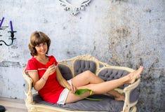 Muchacha en el sofá con una flor roja Foto de archivo libre de regalías