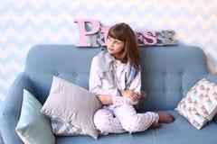 Muchacha en el sofá en pijamas con las almohadas Fotografía de archivo