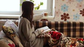 Muchacha en el sofá que lee un libro almacen de video