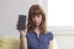 Muchacha en el sofá que muestra una exhibición elegante del teléfono Foto de archivo libre de regalías