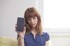 Muchacha en el sofá que muestra una exhibición elegante del teléfono Foto de archivo