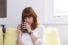 Muchacha en el sofá que se relaja y que bebe Fotos de archivo libres de regalías