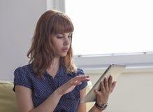 Muchacha en el sofá que trabaja en la tableta Fotos de archivo