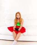 Muchacha en el sofá que juega a los videojuegos Foto de archivo