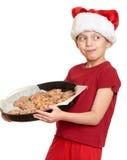 Muchacha en el sombrero con las galletas - concepto de santa de la Navidad de las vacaciones de invierno Imagen de archivo