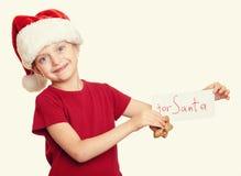 Muchacha en el sombrero con las galletas - concepto de santa de la Navidad de las vacaciones de invierno Imagen de archivo libre de regalías