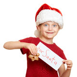 Muchacha en el sombrero con las galletas - concepto de santa de la Navidad de las vacaciones de invierno Fotografía de archivo