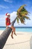 Muchacha en el sombrero de la Navidad que se sienta en una palma Fotos de archivo
