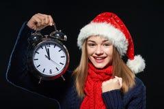 Muchacha en el sombrero de Papá Noel con el despertador Fotos de archivo libres de regalías