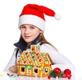 Muchacha en el sombrero de Papá Noel con la casa de pan de jengibre Fotografía de archivo