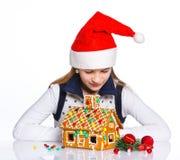 Muchacha en el sombrero de Papá Noel con la casa de pan de jengibre Foto de archivo