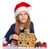Muchacha en el sombrero de Papá Noel con la casa de pan de jengibre Imagen de archivo