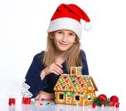 Muchacha en el sombrero de Papá Noel con la casa de pan de jengibre Foto de archivo libre de regalías