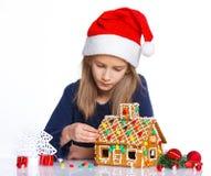 Muchacha en el sombrero de Papá Noel con la casa de pan de jengibre Fotos de archivo
