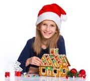 Muchacha en el sombrero de Papá Noel con la casa de pan de jengibre Fotos de archivo libres de regalías