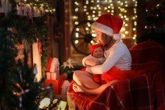 Muchacha en el sombrero de Papá Noel con la muñeca preferida del juguete por la chimenea, Christm Imágenes de archivo libres de regalías