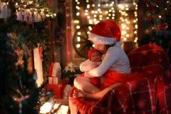 Muchacha en el sombrero de Papá Noel con la muñeca preferida del juguete por la chimenea, Christm Fotografía de archivo libre de regalías