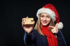 Muchacha en el sombrero de Papá Noel con la tarjeta del crédito en blanco Fotos de archivo libres de regalías