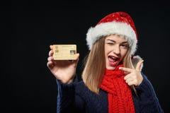 Muchacha en el sombrero de Papá Noel con la tarjeta del crédito en blanco Foto de archivo libre de regalías