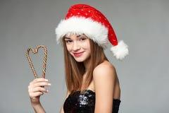 Muchacha en el sombrero de Papá Noel que sostiene los caramelos de la Navidad en forma del corazón Foto de archivo