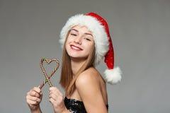 Muchacha en el sombrero de Papá Noel que sostiene los caramelos de la Navidad en forma del corazón Fotos de archivo libres de regalías
