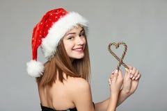 Muchacha en el sombrero de Papá Noel que sostiene los caramelos de la Navidad en forma del corazón Fotos de archivo