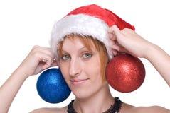 Muchacha en el sombrero de Papá Noel y la bola de la decoración Imágenes de archivo libres de regalías